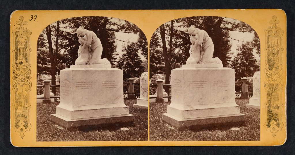 Stereoview of marble pedestal monument with kneeling woman and child, side view.