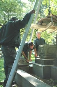 Preservation staff moving a monument into place