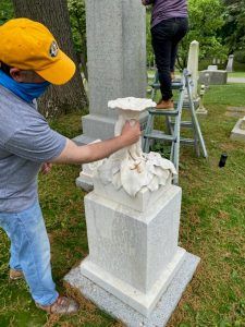 Man in yellow hat repairs white marble monument topped with delicate flower sculpture
