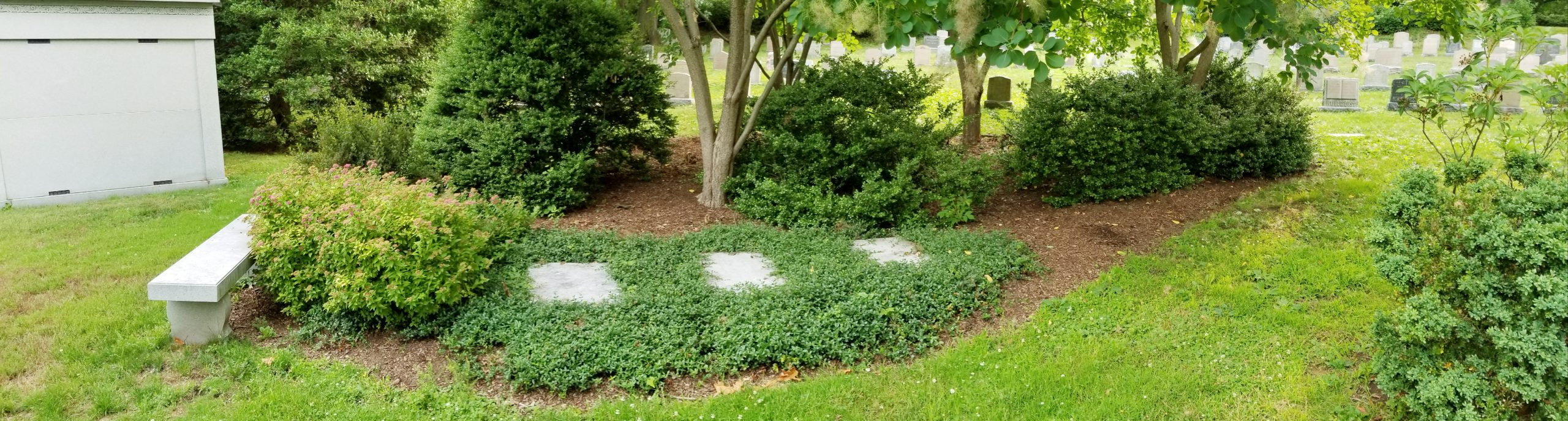 Three granite tablets are set into a bed of groundcover and surrounded by ornamental trees and shrubs. Names and dates of people buried in the garden are inscribed on the granite stones. A bench at the edge of the garden gives visitors a place to sit.
