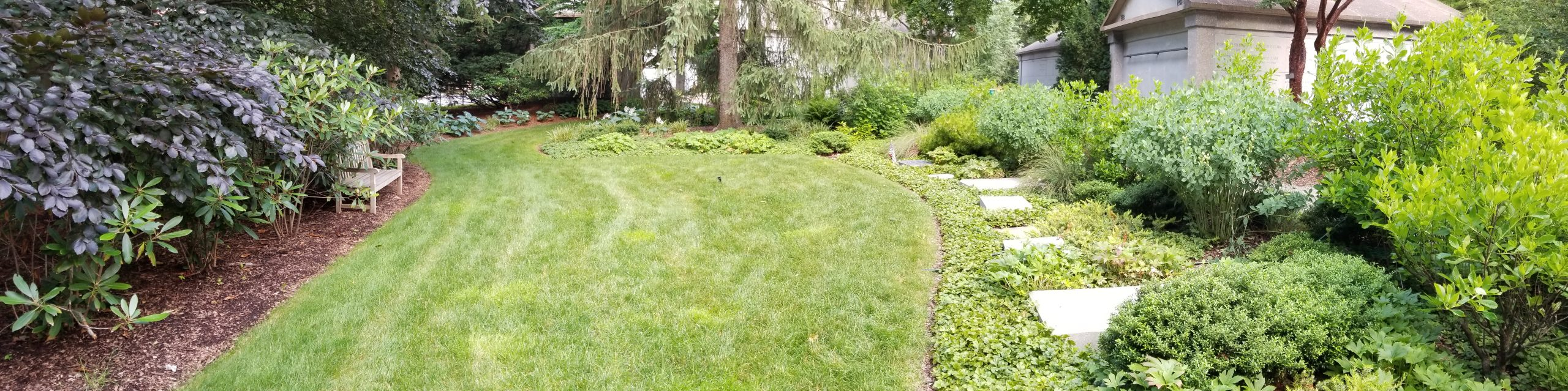 A series of granite ledger stones are set in a bed of groundcovers.
