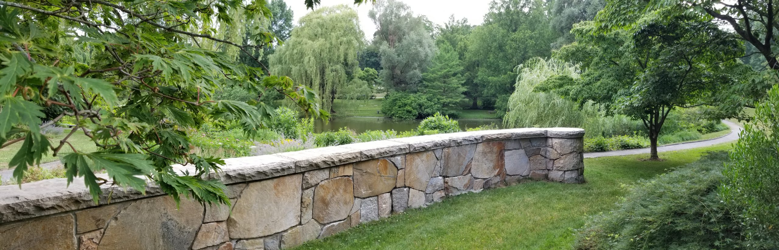 A fieldstone wall overlooks Willow Pond. Individual stones within the wall bear the names and dates of people buried in the ground at the base of the wall.