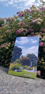 Booklet sitting on a granite ledge with a backdrop of pink flowers and blue sky.