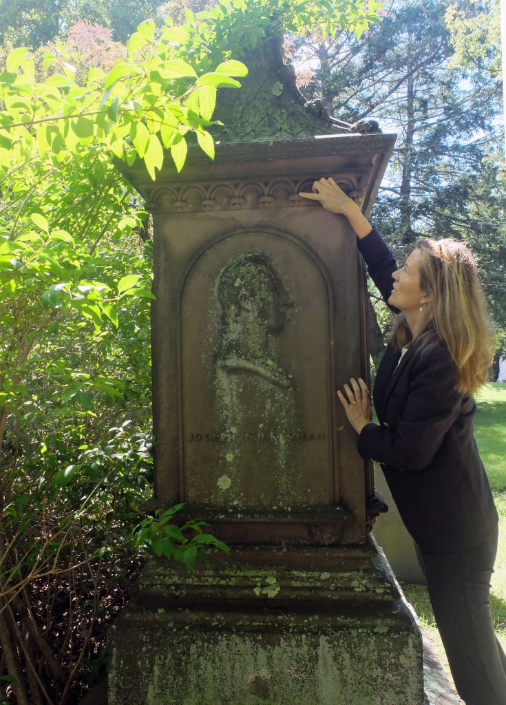 Woman in blue looks at tall brownstone monument