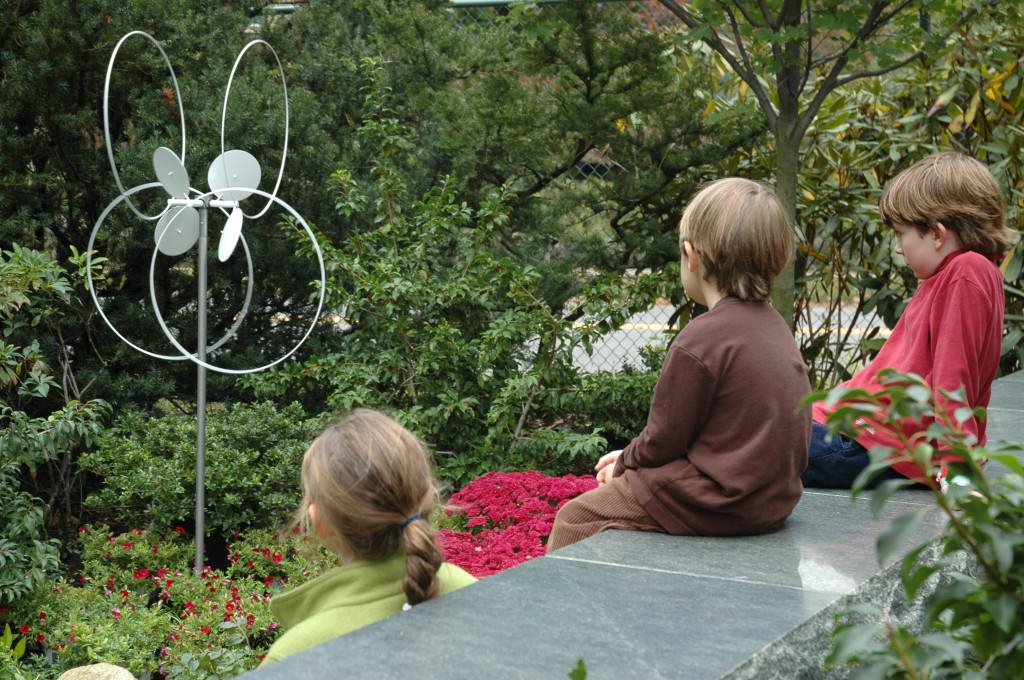 Children watching sculpture move in the wind