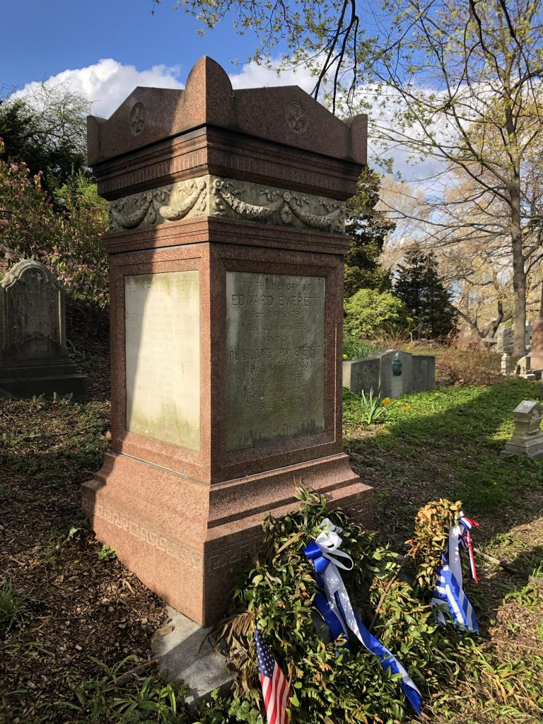 Classical pink granite pedestal monument, inset with marble panels of inscription. Wreaths with blue ribbons and small American flag at the base.