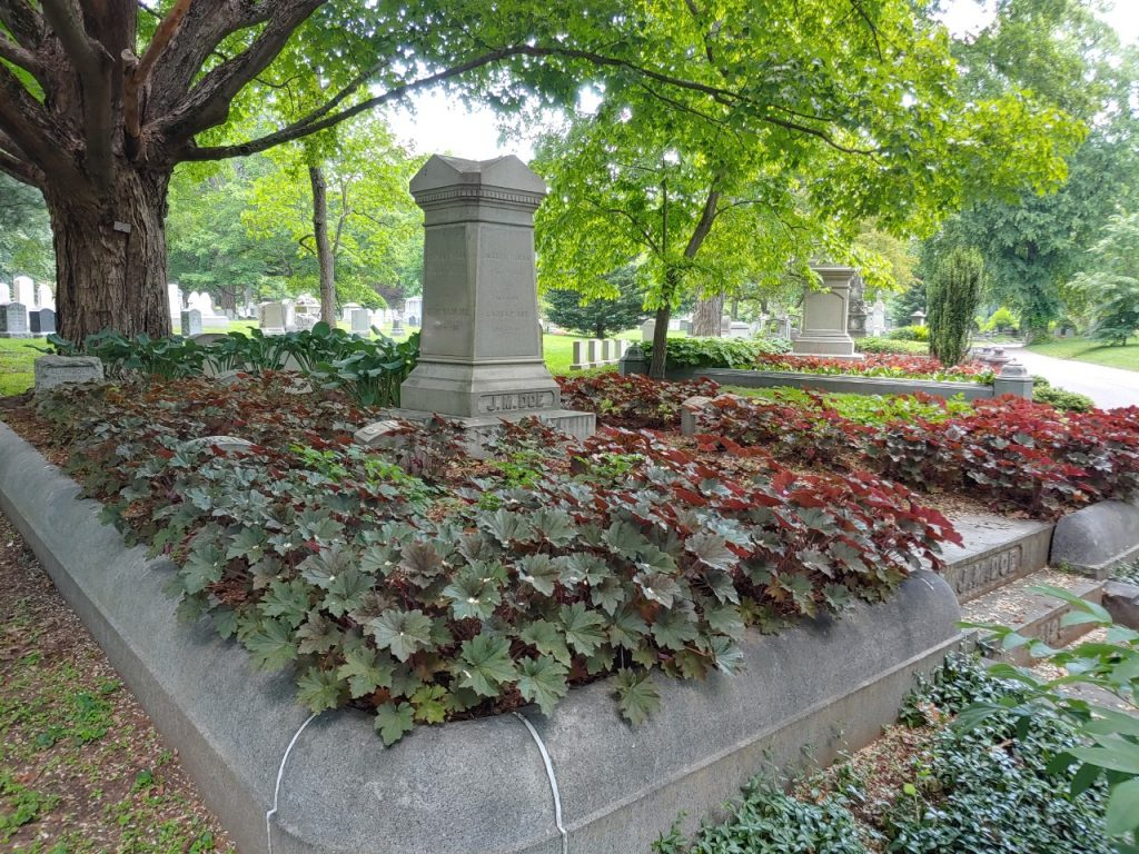 A family lot is surrounded by a 1-foot tall granite wall. A 4 foot high square column sits in the center of the lot. It is surrounded by a ground cover with dark green and maroon leaves.
