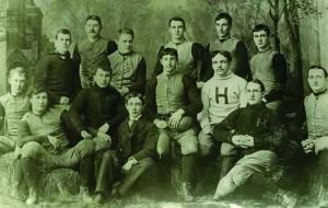 Fourteen young men pose for a group portrait. Thirteen of the men appear to be White and one appears to be Black.