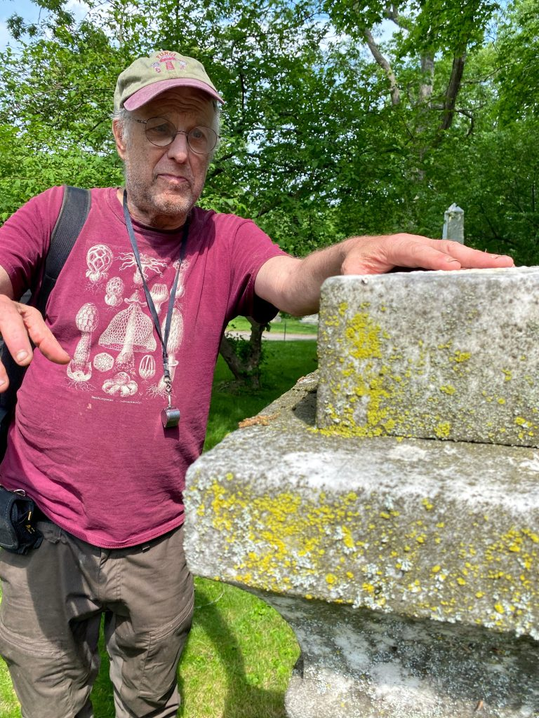 author next to a lichen covered monument