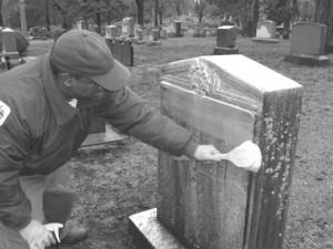 Preservation staff washing a monument by hand